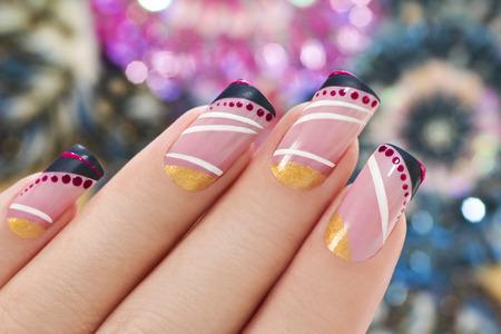 Elegante nail design op een rechthoekige vorm nagels bedekt met licht roze lak met zwart, wit, gouden figuur.