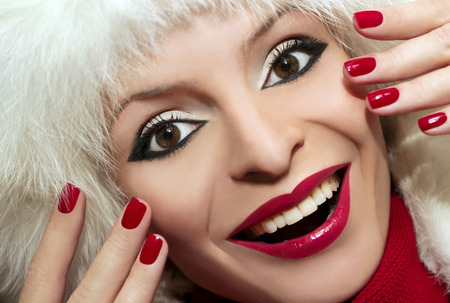 Beautiful makeup for a happy smiling girl with red nail Polish and lipstick. photo