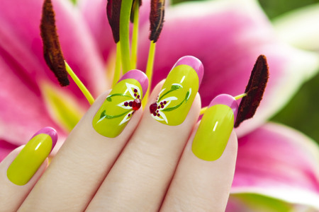 ??????????? ??????? ? ???????? ?????? ?? ???? ?????..   French manicure with a picture of a flower on a background of lilies. photo