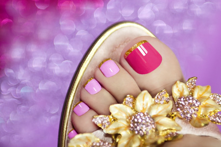 Two-tone pedicure with Golden stripes on the end of the nail in sandals on a brilliant background. Archivio Fotografico
