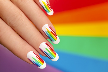 French manicure with bright colored stripes on the background. Rainbow manicure.