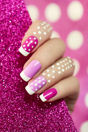 manicure and pedicure: French manicure with pink shades and white dots on a brilliant background.
