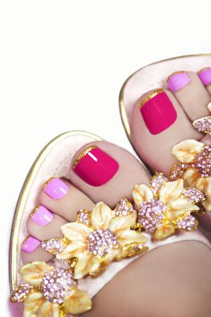 Two-tone pedicure met gouden strepen op het einde van de nagel in sandalen op een schitterende achtergrond.