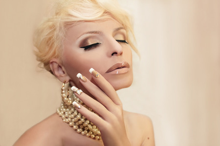 french model: Pearl nails and makeup on the girl with the accessories on a light background.