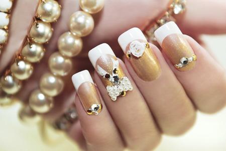 Pearl French manicure met strass-steentjes en versieringen. Stockfoto