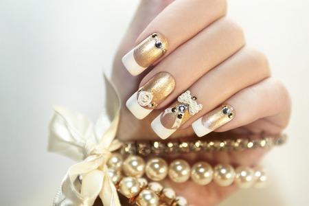 uñas largas: Manicura francesa de perlas con diamantes de imitación y adornos. Foto de archivo