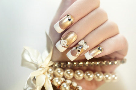 finger nail: Pearl French manicure with rhinestones and embellishments.