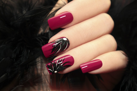 nails art: Burgundy manicure with design on the nails and feathers.