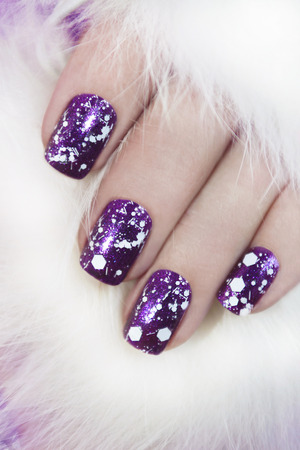 christmas manicure: Lilac nail Polish lacquer with snow crumb on the nails of the girl. Stock Photo