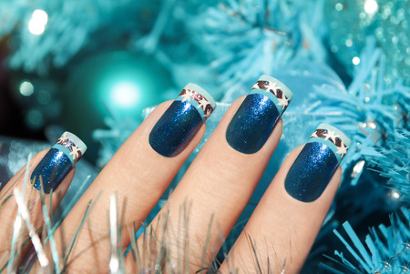 Winter manicure with a pattern in the form of snowflakes on the background of Christmas accessories. Stock Photo