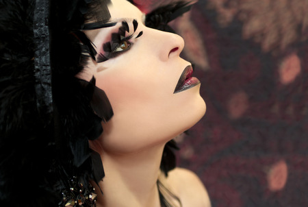 Burgundy makeup with feathers and dark lips on the woman with feathers on his head. photo