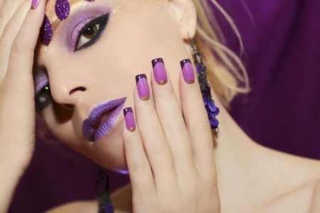 Purple French manicure and makeup on a young woman.