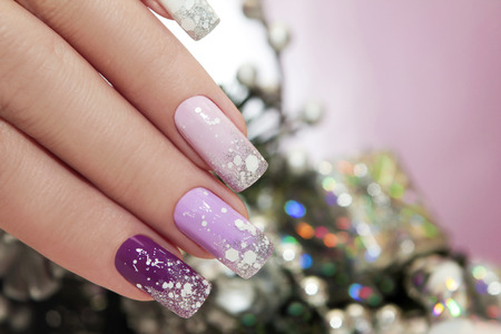 christmas manicure: Lilac nail Polish with sparkles and snowflakes on the background of Christmas tree decorations.