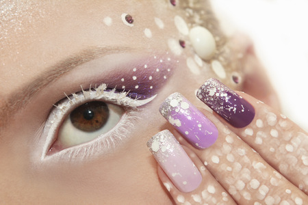 Snow makeup and manicure with glitter and rhinestones in white and purple color. Stock Photo