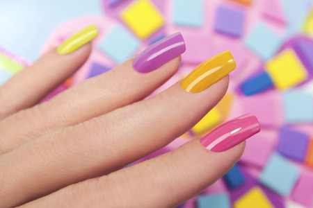 pedicure: Solar nails are covered with multicolored with colored lacquer on the female hand.