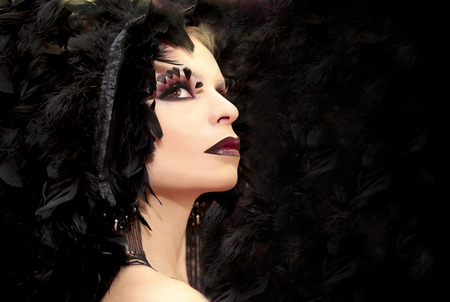 Makeup with feathers on the eyes of the girl in black and red. photo