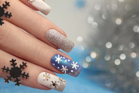 acrylic nails: Manicure with snowflakes on your nails with colored lacquers on a rectangular shaped nails. Stock Photo