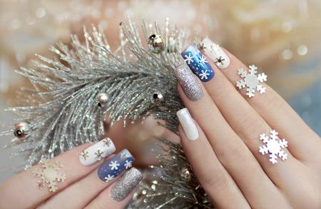 長方形の形をした爪に着色されたラッカーであなたの爪に雪片でマニキュアします。