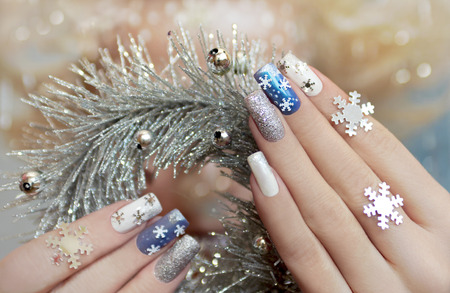 Manicure with snowflakes on your nails with colored lacquers on a rectangular shaped nails. 스톡 콘텐츠