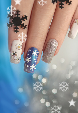 Manicure with snowflakes on your nails with colored lacquers on a rectangular shaped nails. Archivio Fotografico
