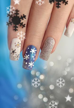 Manicure met sneeuwvlokken op je nagels met gekleurde lakken op een rechthoekig gevormde nagels. Stockfoto