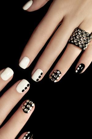 arte moderno: Manicura en las u�as cortas cubiertas con lacado en blanco y negro con pedrer�a en un fondo negro.