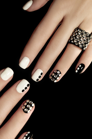 varnish for the nails: Manicure on short nails covered with black and white lacquered with rhinestones on a black background.