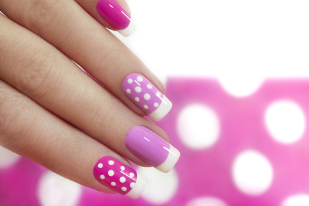 unas largas: Dise�o de u�as con puntos blancos en la manicura francesa con barniz rosa de varios tonos. Foto de archivo