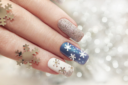 Snow manicure on colored nail Polish with silver snowflakes on a brilliant background.