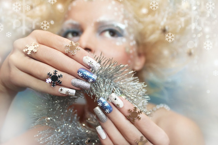 Snow manicure on colored nail Polish with silver snowflakes on the girl.