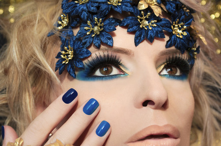 Blue manicure and makeup in festive decoration with glitter in the background.