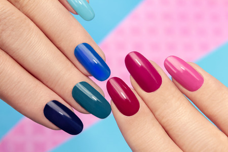 human fingernail: Blue pink nail Polish on long nails on a colored background.