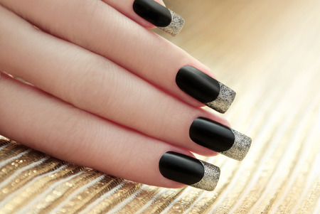 long nail: Black French manicure on Golden striped background. Stock Photo