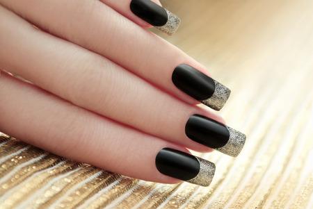 Black French manicure on Golden striped background. Standard-Bild