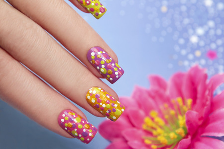 Manicure with multi-colored varnish for the nails and the same design in the form of points on women s hand photo