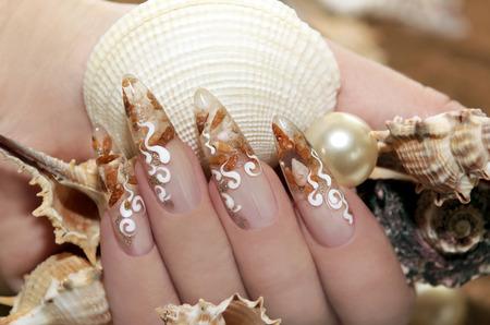 unas largas: Dise�o con peque�as conchas dentro de la u�a y adornos blancos. Foto de archivo
