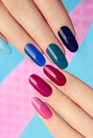 red nail colour: Blue pink nail Polish on long nails on a colored background.