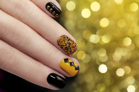 christmas manicure: Caviar manicure in yellow black nails with black and gold rhinestones on a brilliant background.