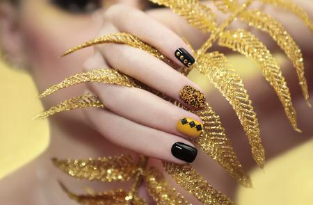 Caviar manicure in yellow black nails with black and gold rhinestones with brilliant ornament in his hand. Archivio Fotografico