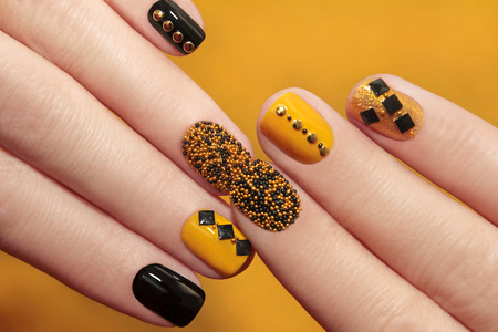 nail art: Caviar manicure in yellow black nails with black and gold rhinestones on a yellow background. Stock Photo