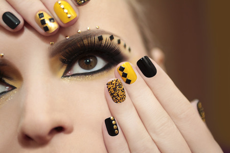 eye lashes: Caviar manicure in yellow and black nail Polish on the girl with false eyelashes and rhinestones of different shapes. Stock Photo