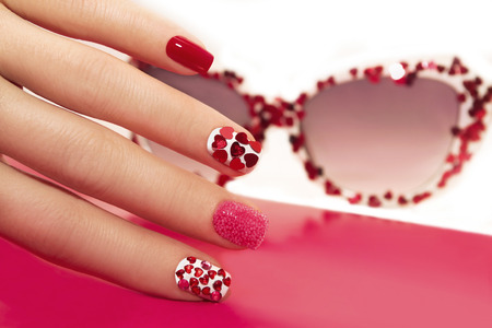 rhinestones: Manicure with rhinestones in the shape of hearts and pink balls on white and red nail Polish.
