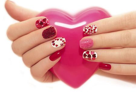 Manicure met steentjes in de vorm van hartjes en roze ballen op witte en rode nagellak op een witte achtergrond.