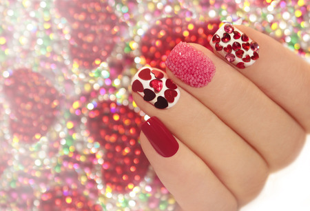 Manicure with rhinestones in the shape of hearts and pink balls on white and red nail Polish on a brilliant background. Archivio Fotografico