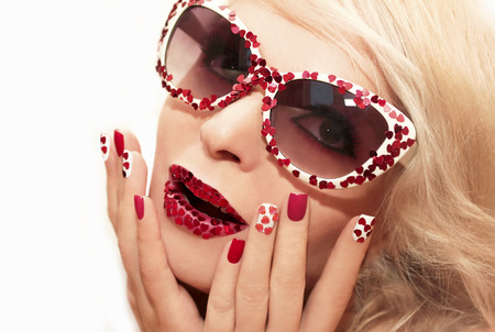Red pink manicure and makeup with hearts on the blonde girl with glasses. Stock Photo
