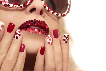 Manicure and lips with hearts of different shapes and colors on the girl with the glasses.