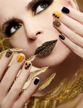 false eyelashes: Caviar manicure in yellow and black nail Polish on the girl with false eyelashes and rhinestones of different shapes. Stock Photo