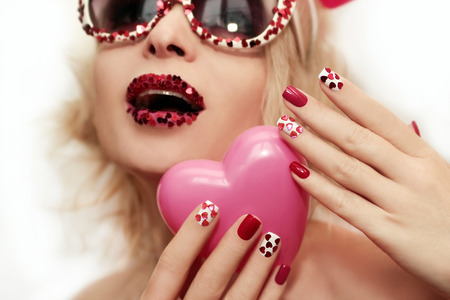 Red pink manicure and makeup with hearts on the blonde girl with glasses. photo