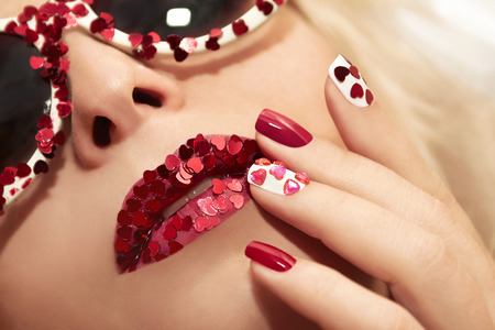 sequins: Manicure and lips with hearts of different shapes and colors on the girl with the glasses.