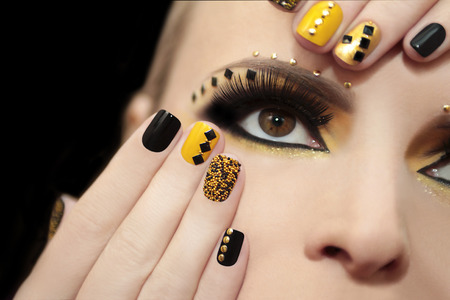 finger nail: Caviar manicure in yellow and black nail Polish on the girl with false eyelashes and rhinestones of different shapes. Stock Photo